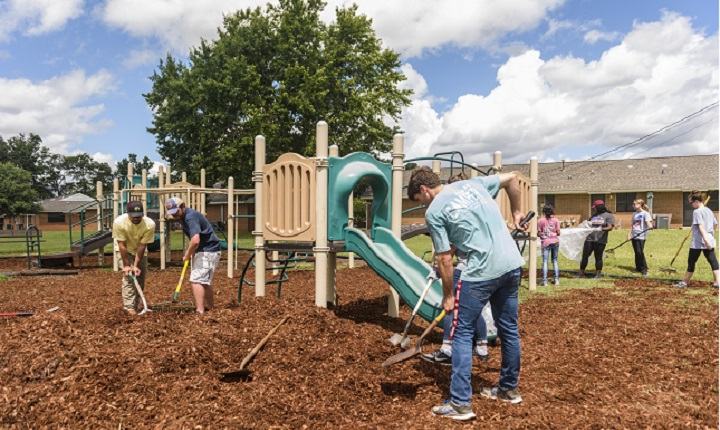 Students shoveling mulch at school playground